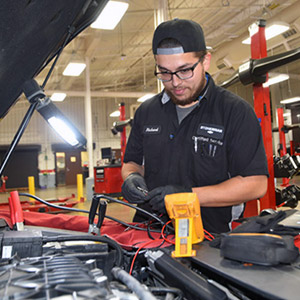 Image of student working on vehicle.