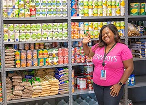 a volunteer stands in front of shelves filled with food at a Dallas College food pantry