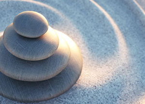 Sunlight shining on four smooth stones stacked on a circular swirl of sand
