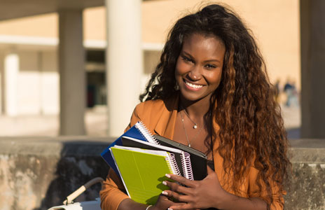 Student smiling and holding spiral notebooks