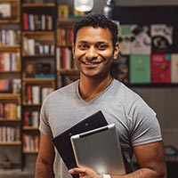 Photo of a student holding a tablet computer and smiling